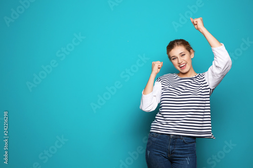 Fotografia  Happy young woman celebrating victory on color background