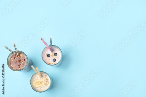 Glasses with different protein shakes on color background, top view. Space for text