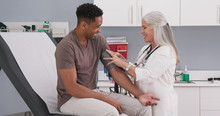 Handsome African-american Patient Seated In Medical Room Having His Blood Pressure Checked By Senior Doctor. Mature White Female Physician Checking Male Patients Blood Pressure In Health Clinic