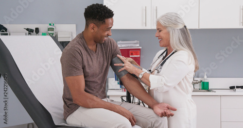 Fotografia  Handsome african-american patient seated in medical room having his blood pressure checked by senior doctor