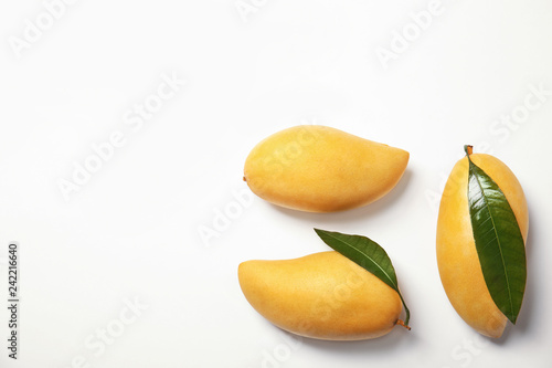 Composition with fresh mango fruits on white background, top view. Space for text