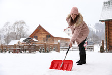 Young Woman Cleaning Snow With Shovel Near Her House. Space For Text