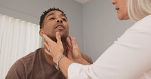 Mature Female Doctor Checking Male Patients Neck For Swollen Thyroid Or Lymph Nodes. Senior Doctor Examining Patients Neck Indoors Medical Clinic