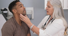 Close Up Of Senior Female Doctor Examining Male Patients Neck. Portrait Of Attractive Black Male Having Doctor Checkup At Health Clinic