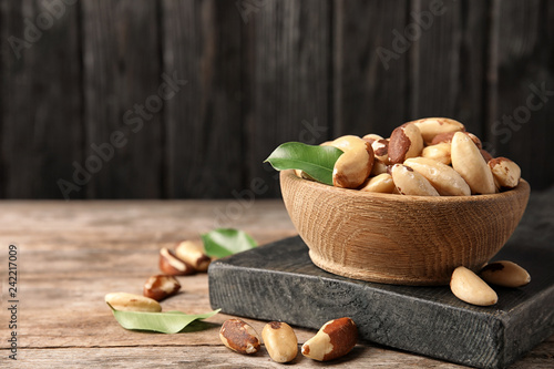 Wooden board with bowl of tasty Brazil nuts on table. Space for text