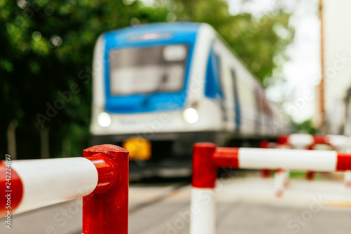 Valokuvatapetti Close-up macro of railway crossing pedestrian fence with train passing quickly