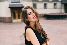 Portrait Of Pretty Girl With Long Curly Hair Posing To Camera On Street On Old Building Background. She Wears Black Dress, Vinous Lips. Hair Covers Half Her Face, She Is Smiling.