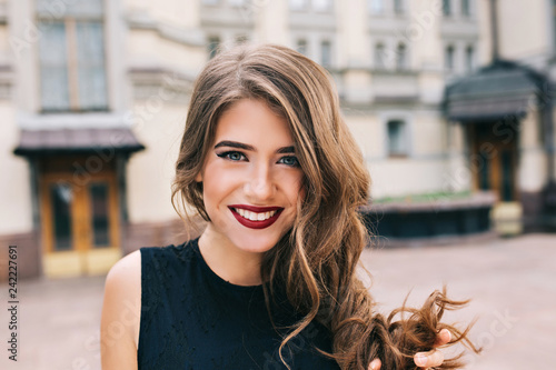 Obraz Closeup portrait of effective girl with long curly hair smiling to camera on street on building background. She wears black dress, vinous  lips. - fototapety do salonu