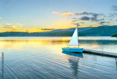 Fotografia  Lonely sailboat in the beautiful sunset with sun stars shines from sky and the s