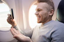 Traveler Tourist Man Is Watching Video On Phone By Plane.