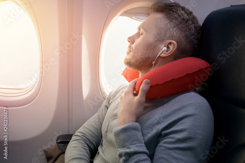Cuadros en Lienzo  Male passenger of airplane listens to music and enjoys pillow for sleeping in chair