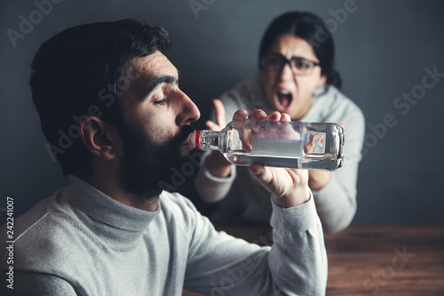 Poster de jardin Bar angry woman with alcohol bottle man