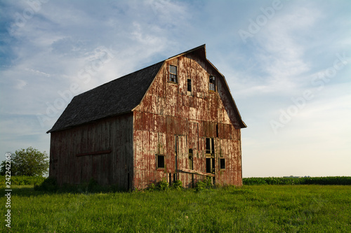 Fotografie, Obraz  Old wooden red barn in the rural countryside as the sun starts to set