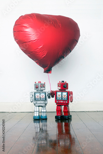 Photo  two retro tin robots together holding a red balloon standing