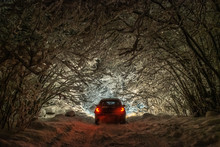 Car Stands Under Bushes And Branches Of Trees Covered With Snow Leaning Over The Road In The Night In Heavy Snowfall