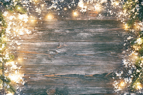 Carta da parati  Fir branches, snow and garland lights on wooden table