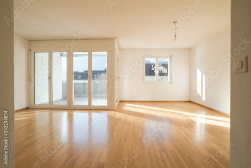 Stampa su Tela bright new living room in an empty apartment with french doors and parquet woode