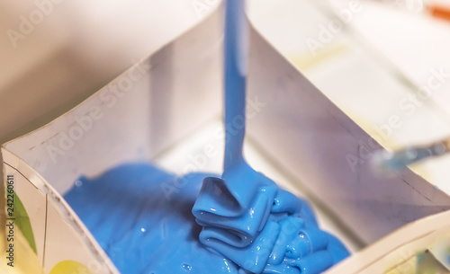 Leinwand Poster Process of putting blue liquid silicone rubber into mold form for making copies