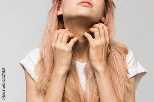 Pinturas sobre lienzo  Isolated studio portrait of young beautiful woman in white t-shirt scratching neck with both hands/irritation, sensitive skin, allergy symptoms, rhinitis, cold, itch, healthcare and medicine concept