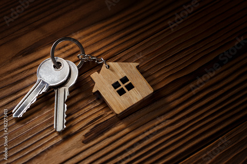 Photo  House keys with house shaped keychain on wooden background