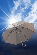 Umbrella On A Blue Sky With Clouds And Sun Rays