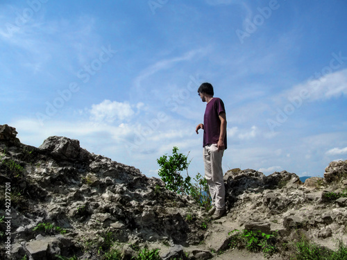 Fotografija  A tall dark-haired young man stands on a rock and looks down - view from the back