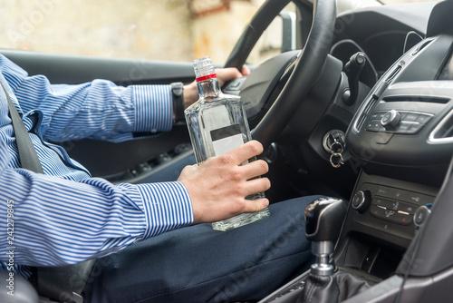 Fotografering  Bottle of alcohol beverage in man's hands