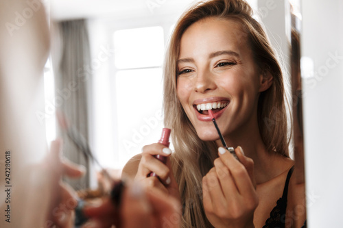Young woman in lingerie underwear looking at mirror apply her lipstick lip gloss doing makeup Canvas-taulu