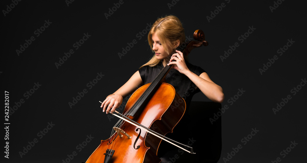 Fototapeta Young girl playing the cello on isolated black background