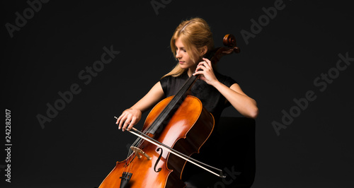 Young girl playing the cello on isolated black background Fotobehang