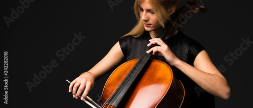 Young girl playing the cello on isolated black background Fototapete