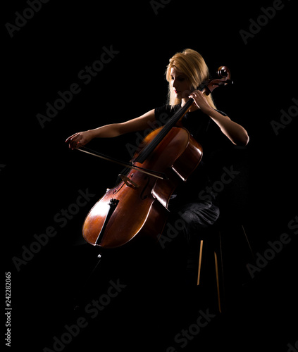 Photo Young girl playing the cello on isolated black background