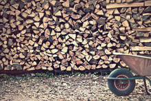Front View Of Pile Of Wood Logs Vintage Effect, A Wheelbarrow Is On The Right