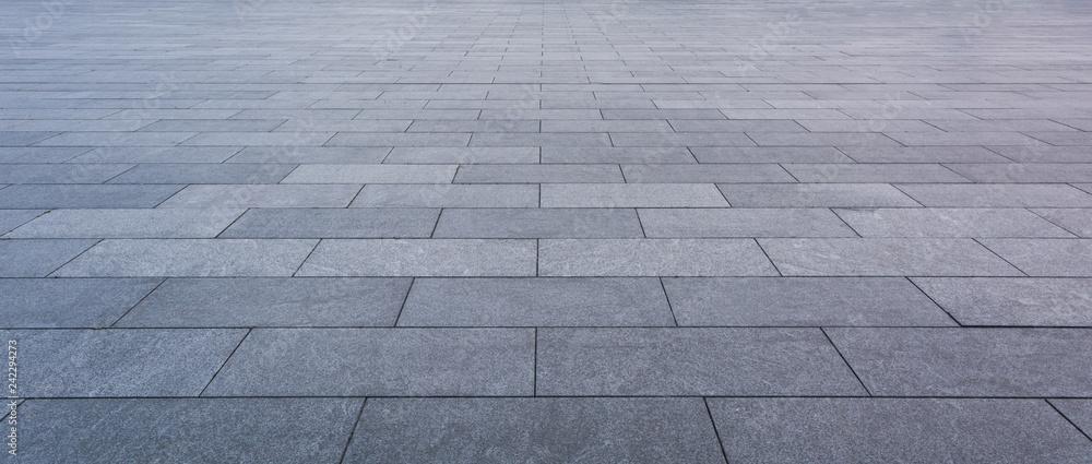Fototapeta Grey brick stone street road. Light sidewalk, pavement texture