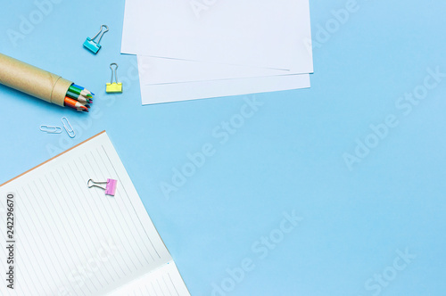 Fototapeta Wooden colored pencils, clean school notebook in line, paper clips on blue background top view flat lay copy space. Pencils for drawing, objects for creativity. Back to school concept. obraz na płótnie