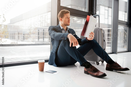 Fototapety, obrazy: Young man sit on floor and look at cafe menu. Cup of coffee stand on floor with tickets in passport. He wait for flight.