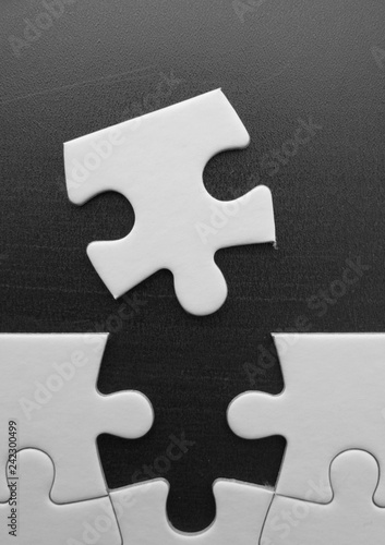 Fotografía  Single piece of a blank jigsaw puzzle removed from or about to be added to the edge of the puzzle