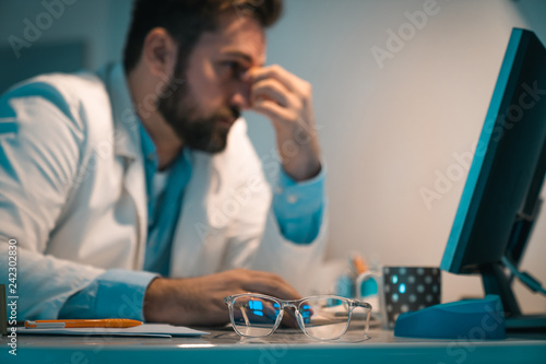 Overworked doctor working late night at office Wallpaper Mural