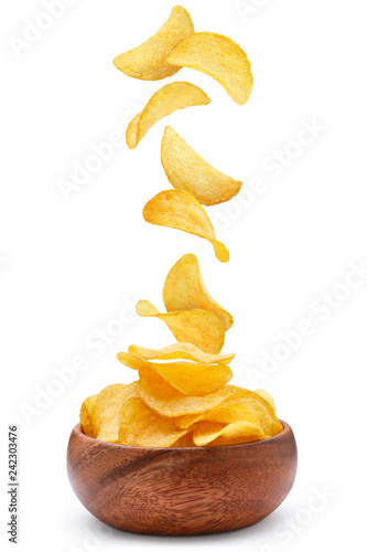 Fotografia Delicious potato chips falling into a wooden bowl, isolated on white background