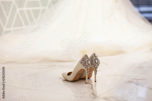Foto op Canvas Bar Elegant wedding shoes on the background of a beautiful long dress