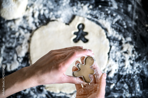 Cookies in the shape of a little man, cut out of dough in the hands of the cook.
