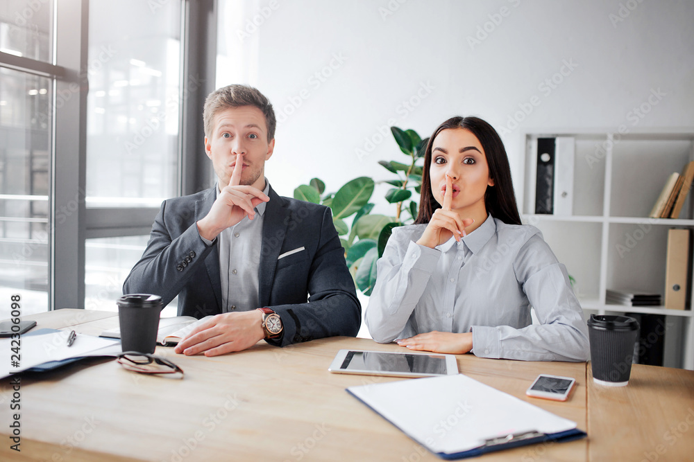 Fototapeta Attentive young man and woman sit at table and look on camera. They are in meeting room. People hold finger on lips. This is hush sign.
