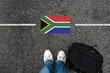 canvas print picture -  a man with a shoes and backpack is standing on asphalt next to flag of South Africa and border