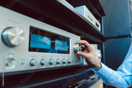 Fotografía Hand von Frau dreht am Hi-Fi Verstärker die Lautstärke hoch