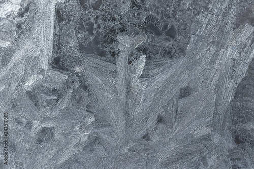 Frosty pattern on the glass. Thin ice crystals on the window gla - 242310803