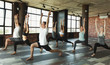 Millennials practising yoga in modern loft studio