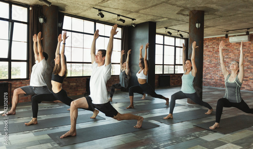 Spoed Foto op Canvas School de yoga Millennials practising yoga in modern loft studio