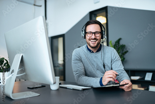 Foto Agent taking notes while talking with customer using headphones and microphone in customer support center