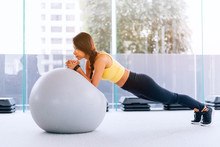 Beautiful Young Asian Woman Training Pilates, Yoga Plank At Gym With Exercise Ball
