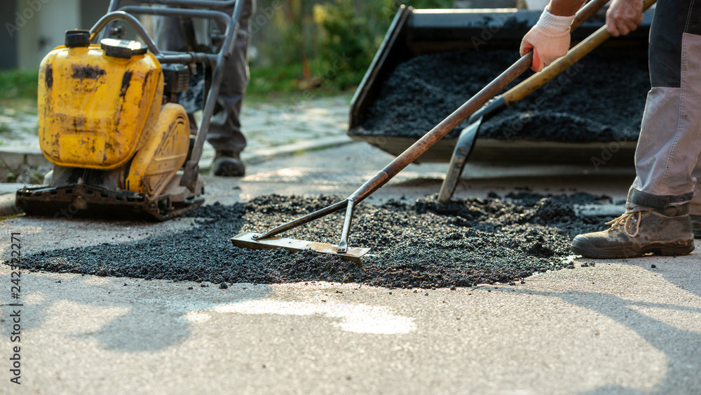 Fototapeta Low angle view of two workers arranging fresh asphalt mix with rakes and shovel